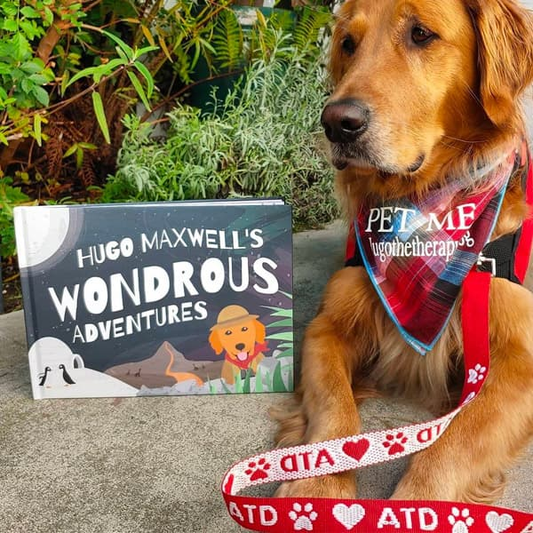 Hugo Maxwell sits proudly next to his Wondrous Adventures Book